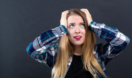 Young woman feeling stressed on a black background