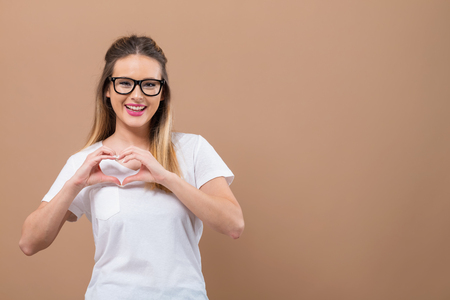 Woman making a heart shaped gesture with her hands on a brown background
