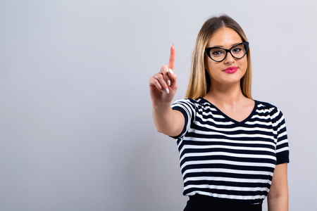 Young woman pointing at something on a gray background Banco de Imagens
