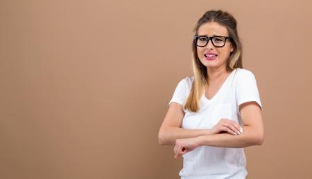 Giovane donna che si gratta il braccio pruriginoso. Problema di pelle. su sfondo marrone