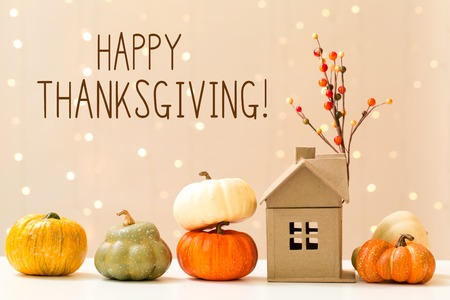 Thanksgiving message with collection of autumn pumpkins with a toy house Stock Photo