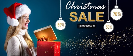 Christmas sale message with young woman with Santa hat opening a gift box