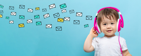 Many emails with toddler boy with headphones on a blue background Stock Photo