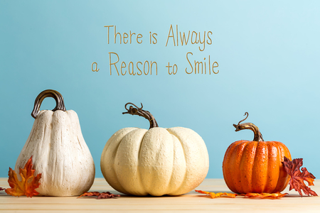 There is always a reason to smile message with pumpkins on a blue background Фото со стока