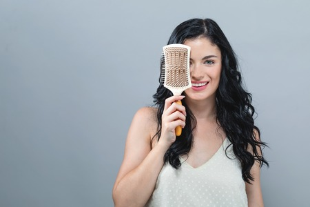 Beautiful young woman holding a hairbrush on a gray background Stok Fotoğraf - 111742934