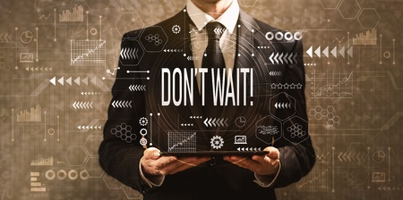 Dont wait with businessman holding a tablet computer on a dark vintage background