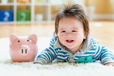 Baby boy with a piggy bank in childcare costs or savings theme