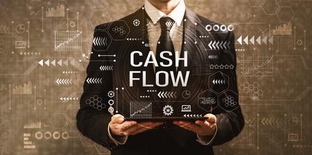 Cashflow met zakenman die een tabletcomputer op een donkere vintage achtergrond houdt