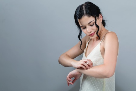 Young woman scratching her itchy arm. Skin problem. on a gray background Stockfoto