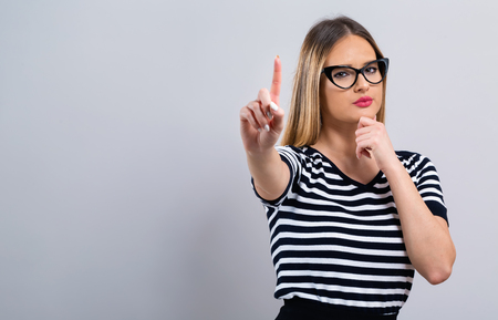 Young woman pointing at something on a gray background Banco de Imagens - 111744879