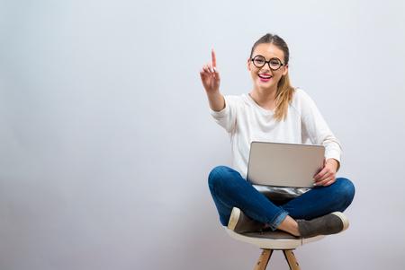 Giovane donna con un computer portatile che indica qualcosa su uno sfondo grigio Archivio Fotografico