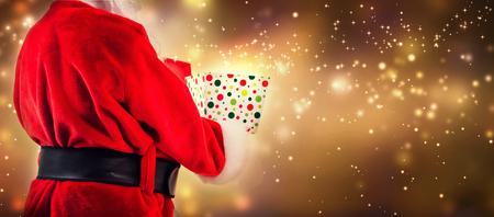 Santa opening a gift box on a shiny light background 스톡 콘텐츠