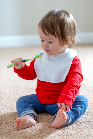Toddler boy brushing his teeth with a toothbrush Stock Photo - 111744970