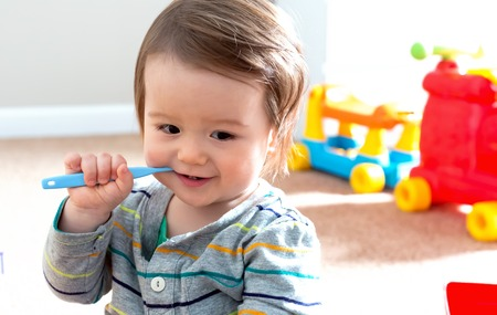 Toddler boy brushing his teeth with a toothbrush Stock Photo - 111777622