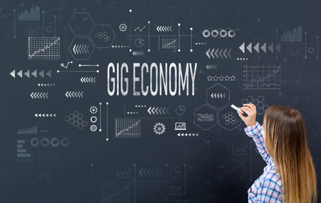Gig economy with young woman writing on a blackboard Stock Photo