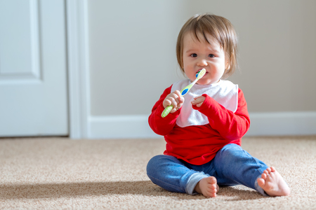 Toddler boy brushing his teeth with a toothbrush Stock Photo - 111778421