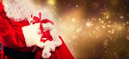Père Noël tenant une boîte cadeau d'un sac rouge sur fond clair brillant Banque d'images