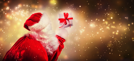 Santa holding a Christmas gift on a shiny light background