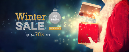 Winter sale message with Santa opening a gift box on a shiny light background