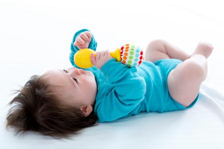 Piccolo neonato che gioca con i suoi giocattoli