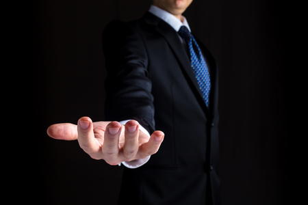 Man in a business suit holding his hand out and showing something Imagens