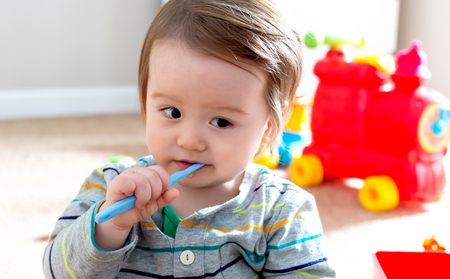 Toddler boy brushing his teeth with a toothbrush Stock Photo - 111781390