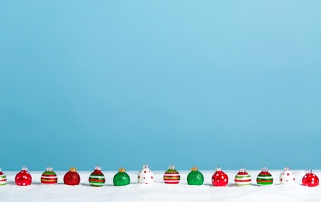Line of little bauble ornaments on a snow mound