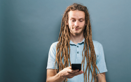 Happy man staring at his cellphone on a gray background