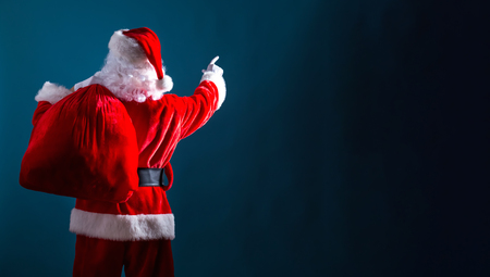 Santa pointing at the sky on a dark blue background