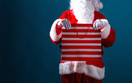 Santa holding a shopping bag on a dark blue background