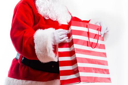 Santa holding a shopping bag isolated on white background Imagens