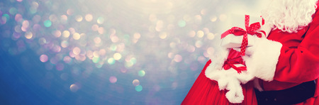 Santa holding a present box from a red sack on a shiny light background 스톡 콘텐츠