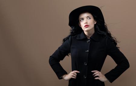 Belle jeune femme dans un manteau à la mode sur fond marron