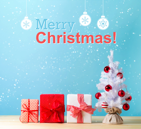 Merry christmas message with a white Christmas tree and gift boxes Foto de archivo