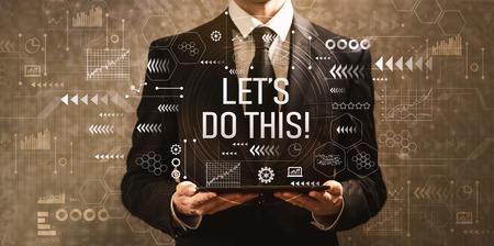 Laten we dit doen met een zakenman die een tabletcomputer vasthoudt op een donkere vintage achtergrond Stockfoto