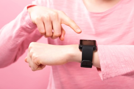 Young woman with a smart watch on a pink background