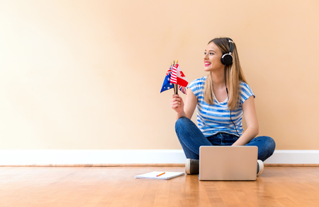 Young woman with English speaking country flags using a laptop computer against a big interior wall Stock Photo