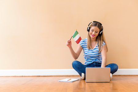Young woman with Italian flag using a laptop computer against a big interior wall