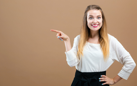 Young woman pointing at something on a brown background