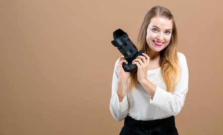 Young woman with a professional digital SLR camera on a brown background 写真素材
