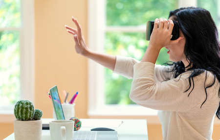 Young woman using a virtual reality headset at a desk in a room