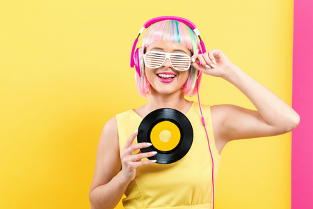 Woman in a colorful wig holding a vinyl record on a split yellow and pink background Imagens