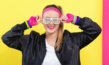 Woman in 1980s fashion with shatter shade glasses on a split yellow and pink background