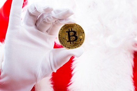 Santa holding a bitcoin isolated on white background
