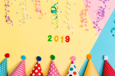 2019 party theme with with hats and streamers on a vibrant background