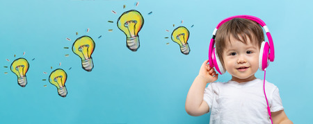 Light bulbs with toddler boy with headphones on a blue background Stock Photo