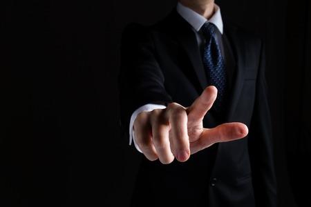 Mann in einem Anzug, der etwas auf schwarzem Hintergrund zeigt oder drückt