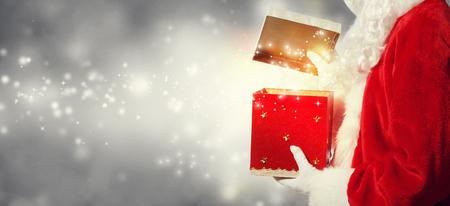 Santa opening a gift box on a shiny light background Stock Photo