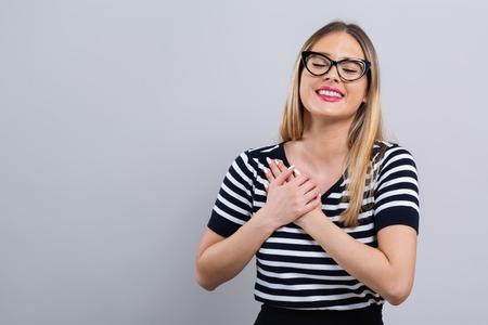 Femme avec une expression sincère sur fond gris