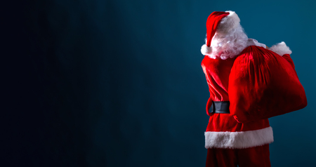 Santa holding a red sack on a dark blue background Stock Photo
